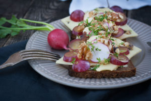 Smørrebrød with two kinds of cheese, radishes and grapes